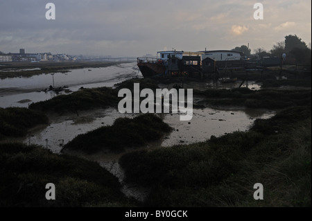 Sun glinting off houseboats at Shoreham-by-sea in west Sussex on the River Adur at low tide - Stock Photo