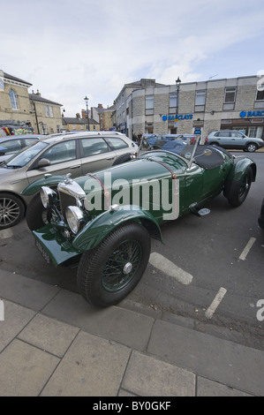 The front of a vintage Bentley car is shown, parked on a street next to more modern vehicles. - Stock Photo