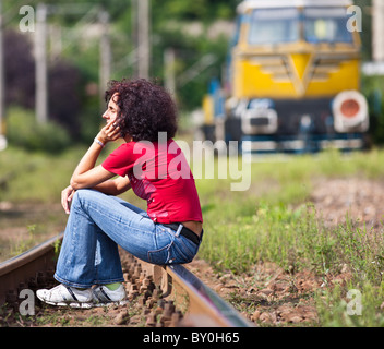 Young redhead woman sitting on rail tracks in a railroad with a locomotive in the background - Stock Photo