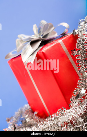 Close-up of Christmas present wrapped in red paper with silver bow on its top - Stock Photo