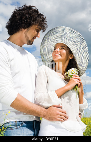Portrait of happy guy hugging tenderly his girlfriend while both looking at each other in summer - Stock Photo