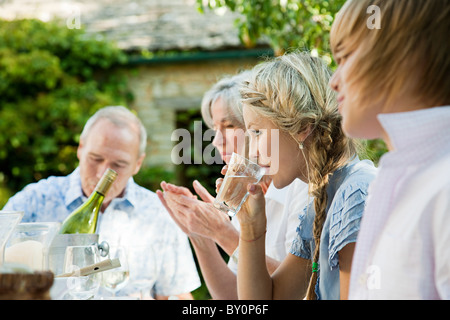 Young woman drinking water with family - Stock Photo