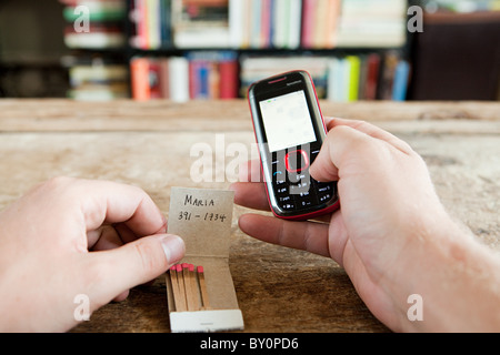 Person calling number written on matchbook - Stock Photo