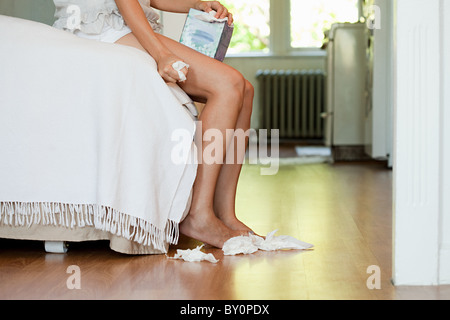 Legs of woman on bed with tissues on floor - Stock Photo