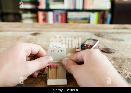 Person holding matchbook with phone number written on it - Stock Photo