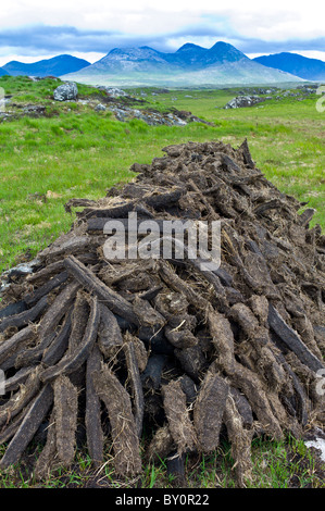 Stacked peat in turf bog on the Old Bog Road near Roundstone, Connemara, County Galway - Stock Photo