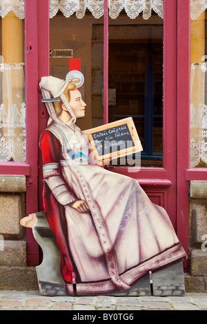 Wooden cutout of woman in Breton costume advertising menu outside cafe restaurant in Quimper Brittany France - Stock Photo