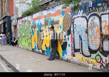 Graffiti covered wall in Brick Lane,Tower Hamlets,London,UK - Stock Photo