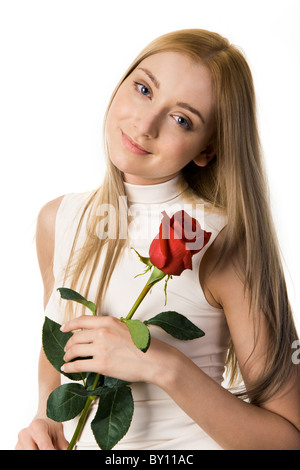 Portrait of beautiful girl holding scarlet rose in hands and looking at camera - Stock Photo
