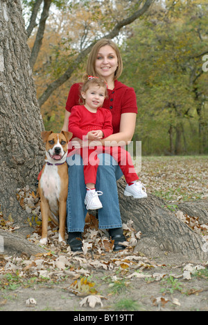 A mother with her toddler daughter at a park with their pet dog. The little girl has bows in her hair and both are - Stock Photo
