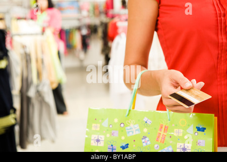 Close-up of woman's hand holding plastic card while going shopping in the mall - Stock Photo