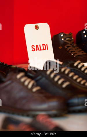 Wintry sales in January, sales discounts cartels displayed  store in hight street center of Rome city Italy shopping - Stock Photo