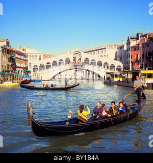 Tourists enjoy a gondola ride on the Grand Canal, Venice, Italy, with the Rialto Bridge in the background. - Stock Photo