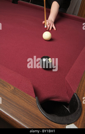 pool player lined up to shoot eight ball in pocket - Stock Photo