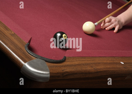 pool player lined up to shoot winning shot in pocket - Stock Photo