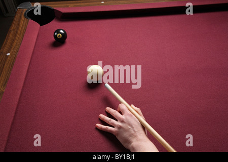 pool table with copy space showing persons arm lined up for winning shot - Stock Photo