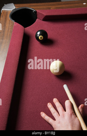 person playing billiards lined up to shoot 8-ball in pocket - Stock Photo