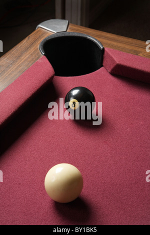 cue and eight ball lined up close on pool table corner pocket - Stock Photo