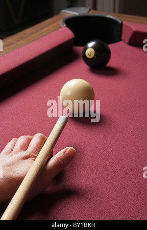 person playing billiards shooting eight ball - Stock Photo