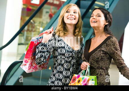 Photo of two happy girls looking at something in the store and laughing - Stock Photo