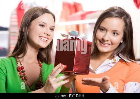Portrait of two girls choosing gifts before Christmas in the mall - Stock Photo