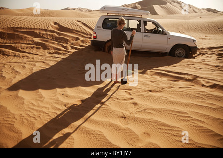 Oman, Empty Quarter. Digging the 4x4 out after getting stuck in the deep sands of the Empty Quarter. MR. - Stock Photo