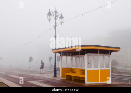 jogging in the fog on the seafront promenade in winter past a shelter - Stock Photo