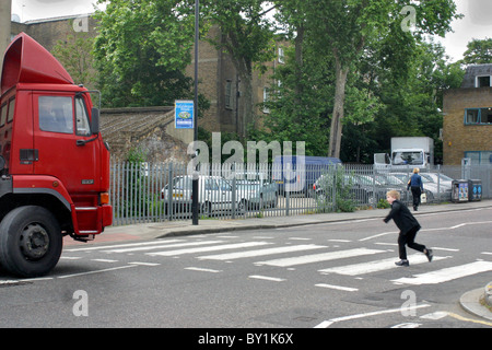 young boy running across zebra crossing with big red transport truck waiting - Stock Photo
