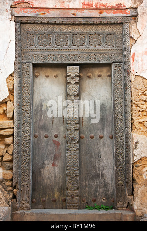 The beautifully carved wooden door frame of a derelict house in Bagamoyo  s main street. When the German colonialists - Stock Photo