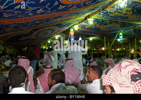 Guests celebrate with dance as other guests look on during a traditional Bedouin wedding celebration. El Tur, Sinai, - Stock Photo