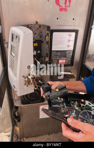 A British Telecom ( BT ) engineer repairs a public payphone in a telephone phone box in the Uk - Stock Photo