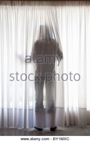 young girl behind net curtains silhouette of figure through curtains stock photo