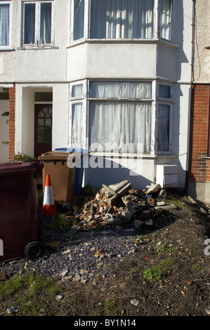Terraced house under renovation with rubbish in front garden. - Stock Photo