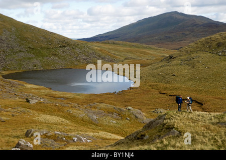 UK, North Wales, Snowdonia.  Man and woman trekking on the flanks of Mt Snowdon.  (MR) - Stock Photo