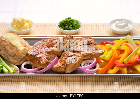 Cooked steak and veggies on a platter with garnishment on the side - Stock Photo