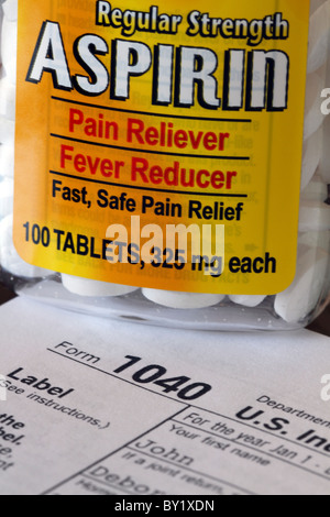 A US Federal Tax Form 1040 with requisite aspirin bottle. - Stock Photo