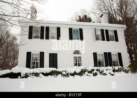 Snow is up to the window sills of a colonial home in Stockbridge, Massachusetts after a major snowstorm. - Stock Photo