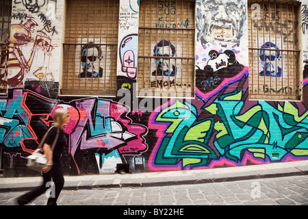 Australia, Victoria, Melbourne.  A woman walks past colourful street art in Hosier Lane. - Stock Photo
