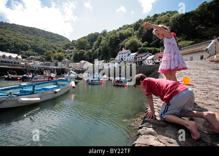 England, Devon, Lynmouth. Children crabbing from the habour wall. (MR) - Stock Photo