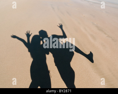 young couple playing with shadow on sand - Stock Photo