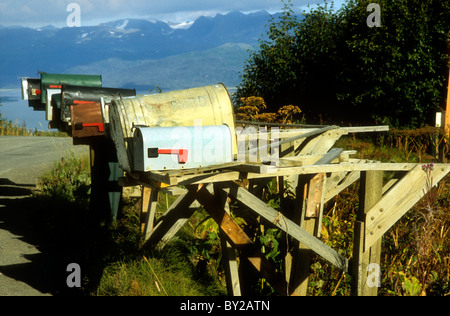 Mailboxes beside East End Road, Homer, Alaska with Kachemak Bay in the background. - Stock Photo