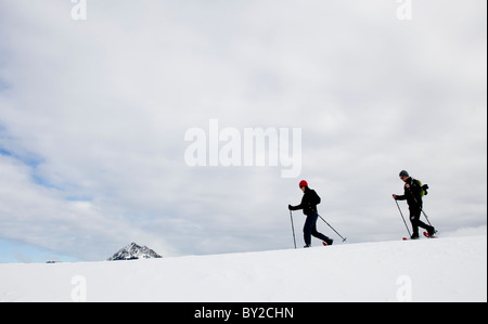 Two people snow shoeing along a ridge on an overcast day. - Stock Photo