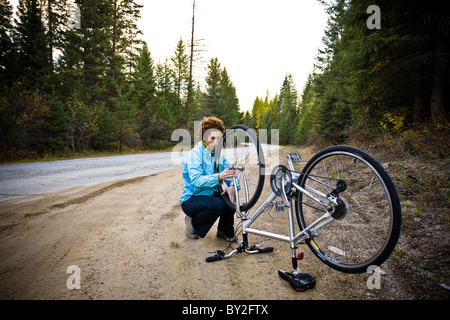 A young woman with red hair fixes her bicycle tire along a rural dirt road. - Stock Photo