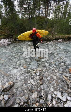 A man carrying a kayak makes his way through a shallow rocky area in the Brandseht River in the western part of - Stock Photo