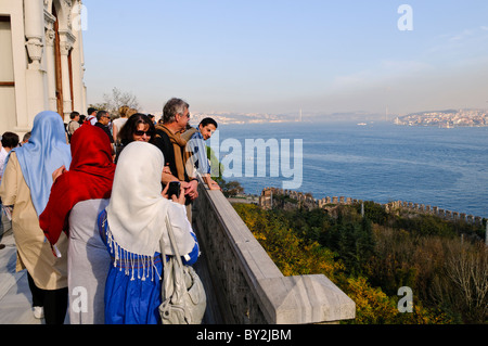 Tourists admire the view from the Topkapi Palace over the Bosphorus. - Stock Photo