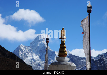 Ama Dablam with a stupa and prayer flags in the Nepali village of Khumjung - Stock Photo