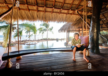 A young boy relaxes and reads a book on the porch of a beachfront house in Mexico. - Stock Photo