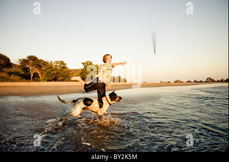 A young boy plays fetch with his dog at sunset on a beach in Mexico. - Stock Photo