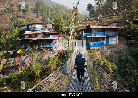 A young man walks across a suspension bridge at Tikhedunga, Annapurna Himalaya, Nepal. - Stock Photo