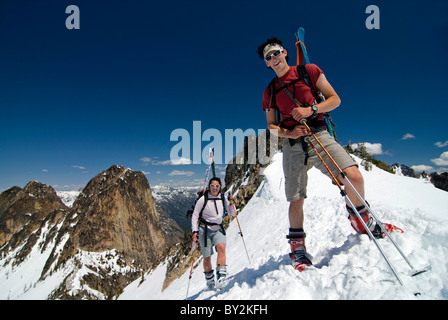 Two backcountry skiers reach a high mountain pass in the North Cascade Mountains, above Washington Pass, on State - Stock Photo